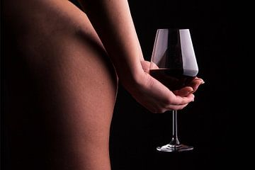 Een foto van een naakte vrouw die een glas wijn vasthoudt achter haar rug.  von Retinas Fotografie