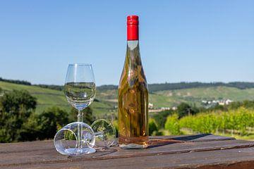 Weinflasche und Weingläser auf einem Holztisch von Reiner Conrad
