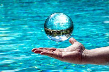 Glaskugel schwebt über einer Hand vor Wasser Hintergrund mit gespiegeltem wolkigem Himmel und Bäumen von Hans-Jürgen Janda
