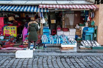 Vrouw bij een vis winkel in Korea van Mickéle Godderis
