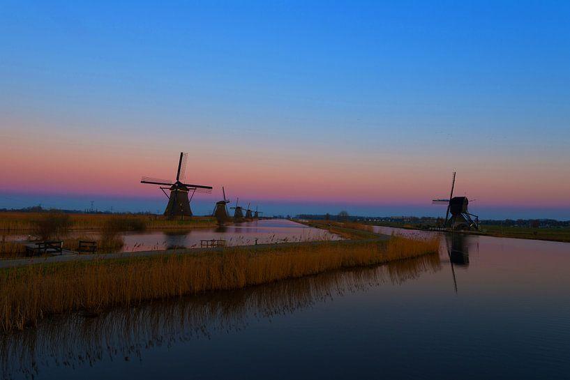 Windmolens langs de Kinderdijk met zonsondergang. van Brian Morgan