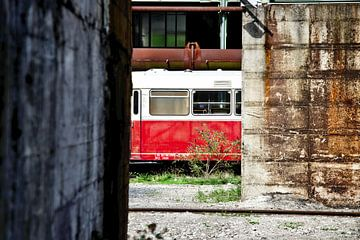 Oude verlaten trein tussen de gebouwen van Jan Brons