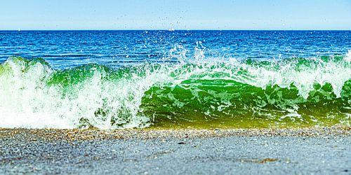 Onstuimige golf breekt op het strand in blauw groene tinten