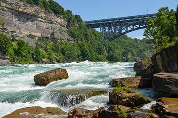 Bruisende stroomversnellingen tussen rotsblokken in een kloof onder een brug van LuCreator