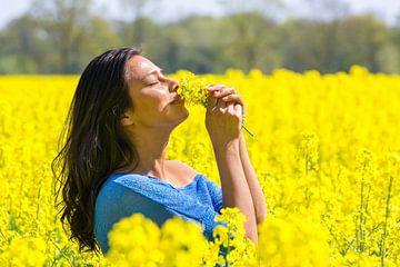Vrouw ruikt aan bloemen in geel koolzaadveld van Ben Schonewille