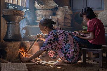Het vuur aanwakkeren van het kooktoestel in de keuken van Anges van der Logt