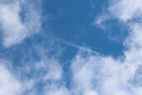 vliegtuig met condensspoor in de wolken