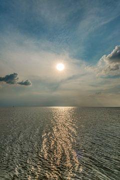 Zon boven het IJsselmeer met een lichte nevel en een lichtbaan op het water van Harrie Muis