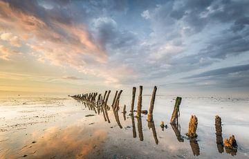 Paaltjes richting de horizon op het Wad bij Wierum Friesland van Martijn van Dellen