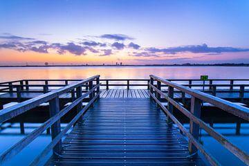 Een steiger aan een meer tijdens een rustige zonsopkomst van Eelco de Jong