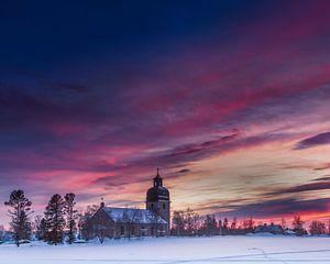 Een kerk gevangen in de zonsondergang van
