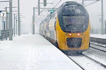 Rijdende trein in een sneeuwstorm bij Centraal Station in Amsterdam van Nisangha Masselink