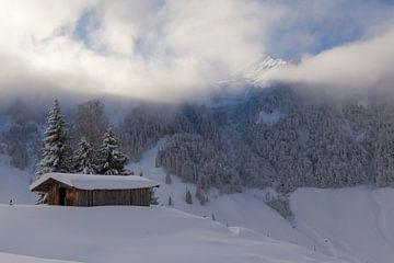 Berghütte im Schnee mit aufziehenden Wolken