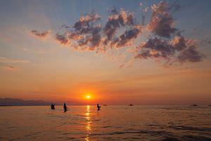 De vissers silhouetteren op het strand bij kleurrijke zonsondergang in Bali, Indonesië