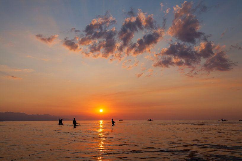 De vissers silhouetteren op het strand bij kleurrijke zonsondergang in Bali, Indonesië van Tjeerd Kruse