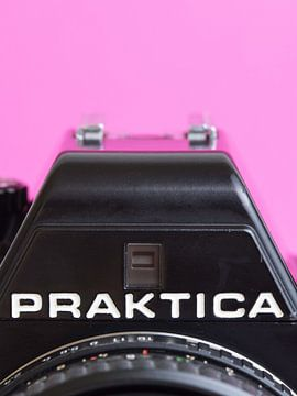 Makro-Nahaufnahme von Details einer alten 'Praktica'-Kamera mit rosa Hintergrund von Iris Koopmans