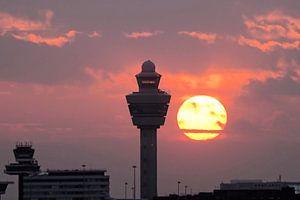 Ondergaande zon naast verkeerstoren Schiphol van