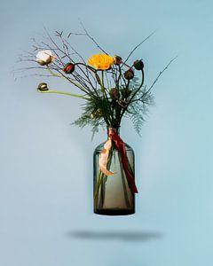 Blumenstrauß in einer schwimmenden Vase vor blauem Hintergrund