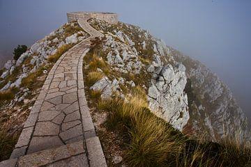 Een kronkelend pad (weg) over een klif. Alles is in een mistwolk, een wolk is een weg over een holte van Michael Semenov