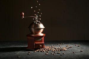 Houten vintage koffiemolen op een leisteenplaat, vallende en liggende gebrande bonen tegen een donke