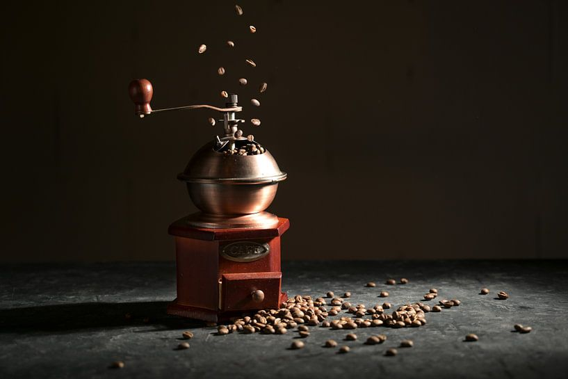 Houten vintage koffiemolen op een leisteenplaat, vallende en liggende gebrande bonen tegen een donke van Maren Winter