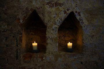 zwei weiß brennende Kerzen in zwei Nischen in einer dunklen alten Backsteinmauer eines Klosters, Kop von Maren Winter
