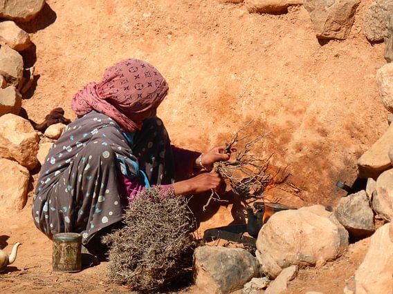 Marokkaans meisje maakt vuur in de woestijn