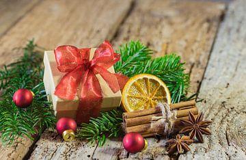 De giftdoos van Kerstmis met rood lint en decoratie op houten lijst van Alex Winter