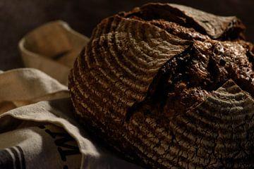 Ovenvers boerenbrood met krokante korst op een doek in jutte van Caro Hum