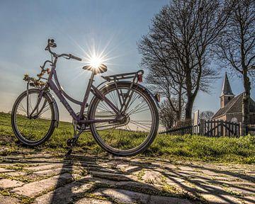 Een damesfiets en het kerkje van Haskerdijken in Friesland. van Harrie Muis