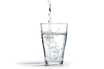 water wordt in een drinkglas gegoten, geïsoleerd op een witte achtergrond met kopieerruimte van Maren Winter