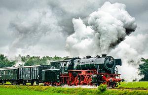 Stoomtrein op het platteland met dikke rookwolken uit locomotief