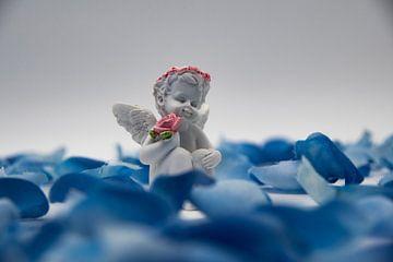 Een engel met een roos in zijn hand met blauwe kunstbloemen van David Esser