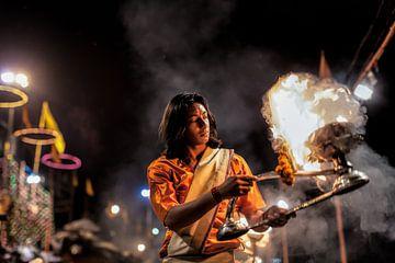 Monnik ontsteekt vuur tijdens hindustaanse ceremonie aan de oever van de Ganges in Varanasi India. W van