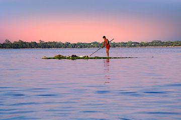 Arbeider verzamelt zeewier uit het water van het Inle Meer in Myanmar bij zonsondergang van