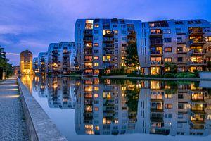 Appartementen weerspiegelen in het water.