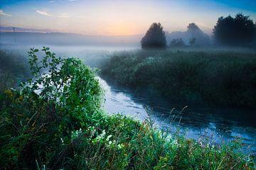 L'aube commence, l'eau bleutée de la rivière à côté des buissons en fleurs, le brouillard au-dessus  sur Michael Semenov