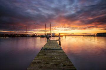 Sonnenuntergang am Museumshafen in Lauwersoog an einem schönen Abend mit einer roten Abendsonne. von Bas Meelker