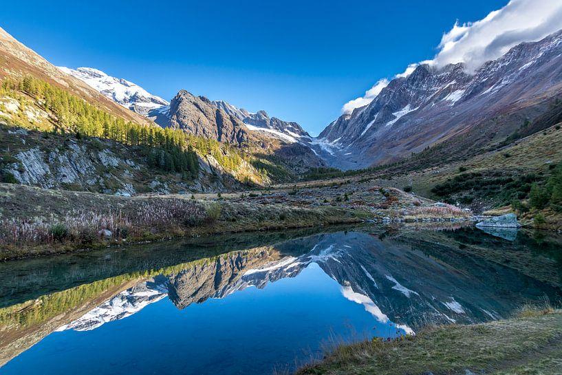 Grundsee met weerspiegeling van de bergen in het Lötschental. van Ad Van Koppen