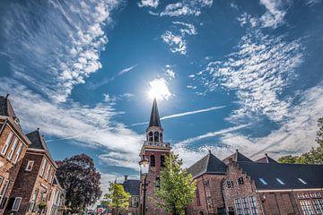 Kerktoren op het plein van Appingedam in het vroege tegenlicht met zon van Harrie Muis