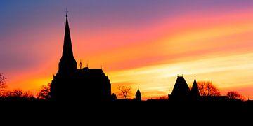Silhouette d'horizon de ville de Kampen au fleuve IJssel pendant le coucher du soleil sur Sjoerd van der Wal