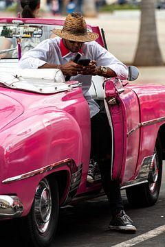 Man met mobiele telefoon in roze oldtimer in Havana van Dieter Walther