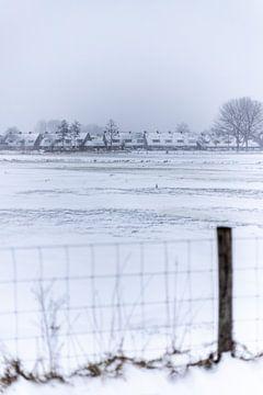 Een Nederlands dorp in de sneeuw achter een hek van Thomas Winters