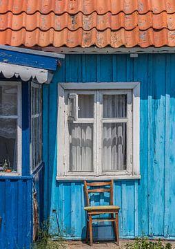 Stuhl vor einem blauen Holzhaus in Nida von Marc Venema