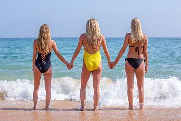 Drei junge blonde Frauen stehen am Strand von