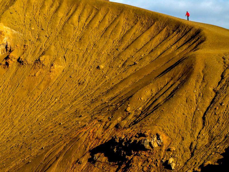 Lopen over de rand van de vulkaankrater van Krafla, IJsland van Rietje Bulthuis