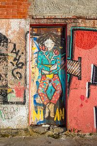 Smalle deur in fabriekspand met graffiti van Wil Wijnen