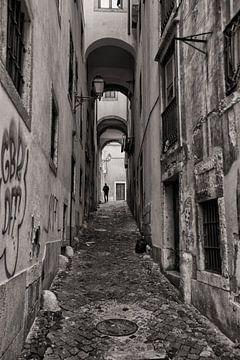 Monochroom beeld van een man die door de smalle starten van Lissabon wandelt. Wout Kok One2expose sur Wout Kok