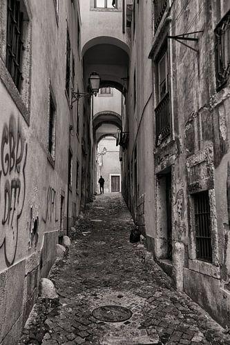 Monochroom beeld van een man die door de smalle starten van Lissabon wandelt. Wout Kok One2expose