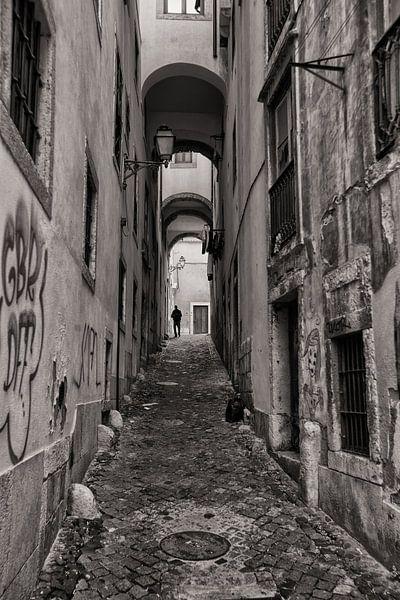 Monochroom beeld van een man die door de smalle starten van Lissabon wandelt. Wout Kok One2expose van Wout Kok